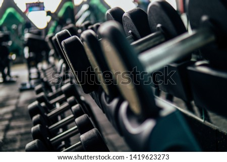 Black dumbbell set Close up many metal dumbbells on rack in gym
