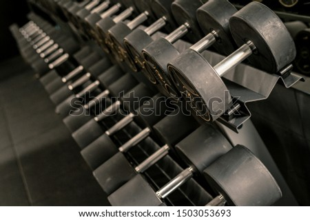 Black dumbbell set. Close up many metal dumbbells on rack in sport fitness center , Weight Training Equipment concept