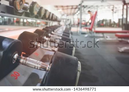 Black dumbbell set. Close up of many metal dumbbells on rack in sport fitness center.