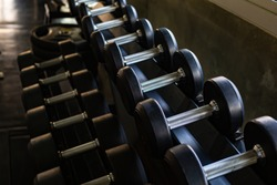 Black dumbbell set. Rows of dumbbells in the gym . Close up many metal dumbbells on rack in sport fitness center , Weight Training Equipment concept.