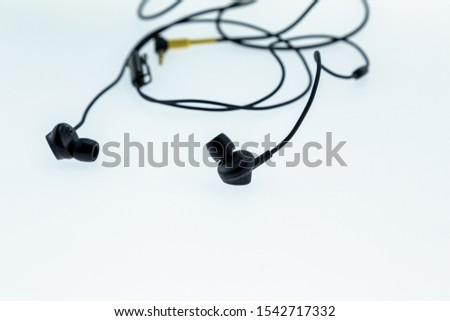 Black Earphone or earphones on white background, Close-up on speaker with copy space.