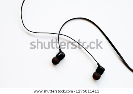 Black earphones on white background or earphones isolated use for mobile phone accessory background