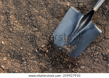 black earth texture with a black metal shovel - stock photo