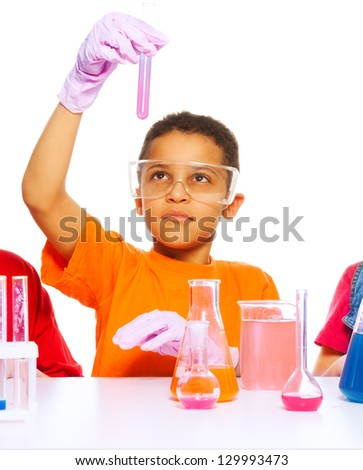 Black eight years old boy analyzing results of science test in the test tube