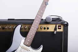 Black electric guitar, amp and mic on white background