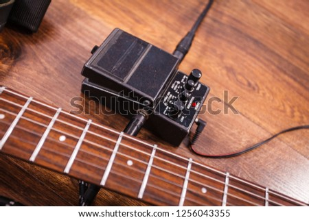 Black electric guitar with equipment and accessories, audio stomp box effects and cables in music studio