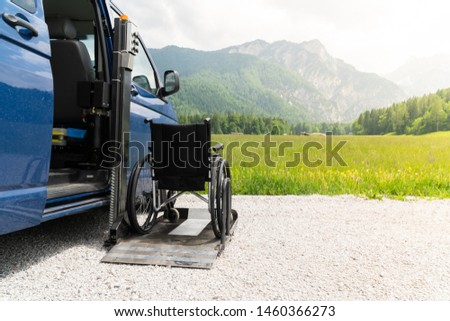 Black electric lift specialized vehicle for people with disabilities. Empty wheelchair on a ramp with nature and mountains in the back