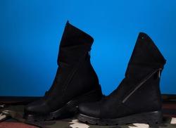 Black Elegant Woman Boots On Dark Blue Vivid Background, Artsy and Stylish Concept, Women's Fashion