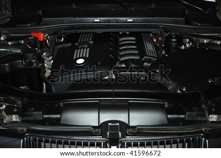 Black engine under the hood of a car