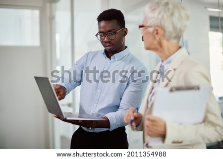 Black entrepreneur communicating with his senior business mentor while working on laptop n the office.  Foto stock ©