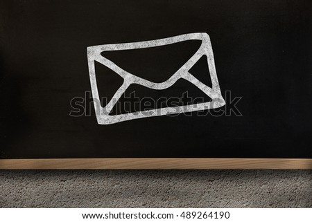 Black envelope drawing against blackboard on wall