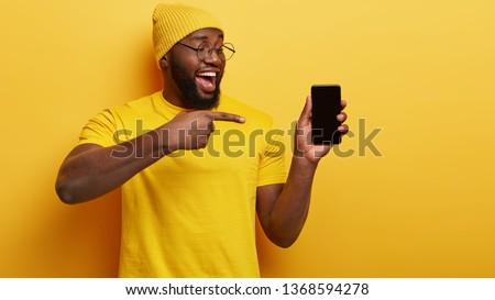 Black ethnic man with thick bristle, points at smart phone device, shows blank screen for your promotional content, wears headgear and casual yellow t shirt, advertizes new device for customers