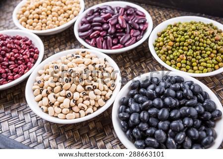Black eye peas, mung bean, adzuki beans, soy beans, black beans and red kidney beans in white bowl on wicker tray