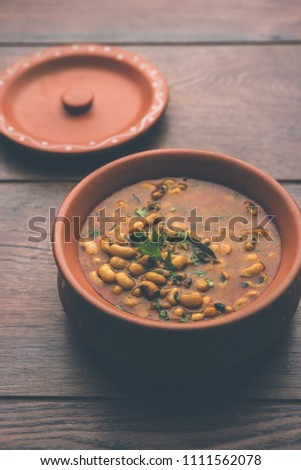 Black Eyed Kidney Beans Curry or Chawli chi usal / Barbati masala, served in a ceramic bowl over moody background, selective focus  #1111562078