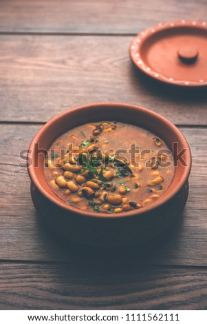 Black Eyed Kidney Beans Curry or Chawli chi usal / Barbati masala, served in a ceramic bowl over moody background, selective focus  #1111562111