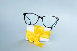 Black Eyeglasses And Small Present on Light Blue Background