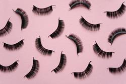 Black false lashes strips on pink background