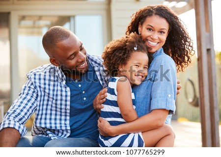 Black family embracing outdoors smiling to camera outside ストックフォト ©