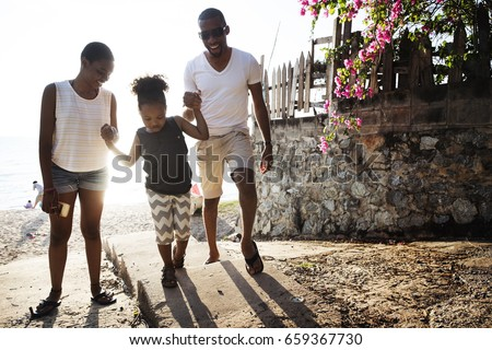 Black family enjoying summer together at the beach