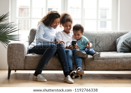 Black family sitting on couch have a fun at home. African mother spend free time with daughter and son using mobile phone taking selfie photo playing new game. Happy family together on weekend concept