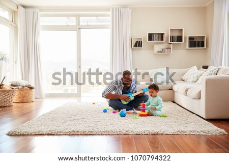 Black father and toddler son playing in the sitting room