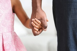 Black father taking his little daughter gently by the hand, giving her warm, safe, protected and comforting feeling, closeup