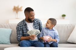 Black Father Teaching His Son Budget Planning And Financial Literacy Putting Money Savings In Piggybank Sitting On Couch Indoors. Personal Finances Concept. African Dad Talking With Kid About Money