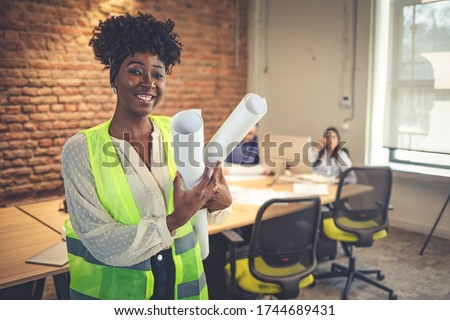 Black female architect smiling in busy office. Female Architect with Blueprints. Portrait of confident young businesswoman holding blueprint in office. Young female entrepreneur
