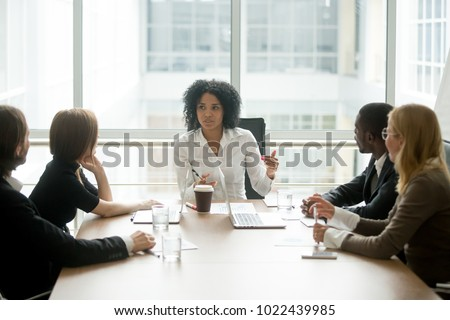 Black female boss leading corporate multiracial team meeting talking to diverse businesspeople, african american woman executive discussing project plan at group multi-ethnic briefing in boardroom #1022439985