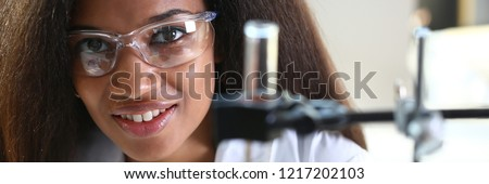 Black female chemist student conducting research using a microscope for bacterial contamination of water searching for a vaccine to treat diseases in medicine doctor concept #1217202103