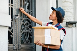 Black female courier knocking on front door while delivering packages.