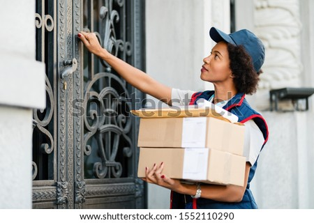 Black female courier knocking on front door while delivering packages.  Stock photo ©