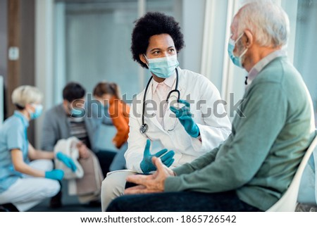 Black female doctor and senior man wearing protective face masks while communicating in a waiting room at hospital.