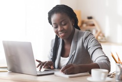 Black female entrepreneur working in office, typing on laptop computer and taking notes, free space