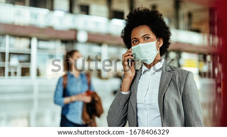 Black female passenger talking on smart phone while wearing face mask at the airport during virus epidemic.