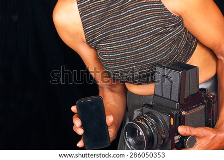 Black female photographer comparing new and old technology