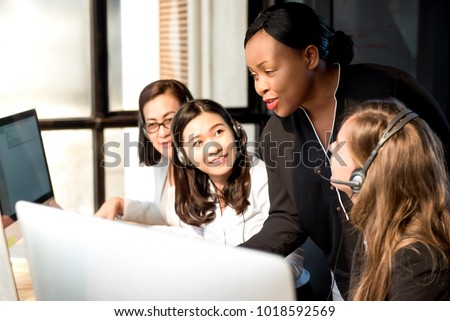Black female supervisor training work to her multiethnic colleagues in call center office