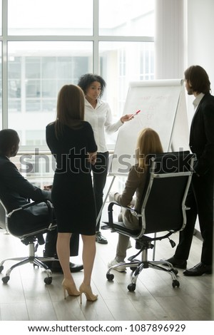 Black female team leader teaching diverse business people at meeting, multiracial executive group listening to african employee explaining new idea with flipchart at corporate training, vertical view stock photo