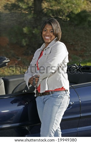 black female teen driver standing with new car