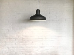 Black fixture of lamp have white bricks wall is background.