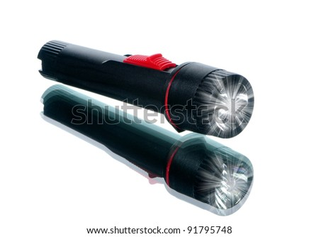 Black flash light with red switch on white with reflection
