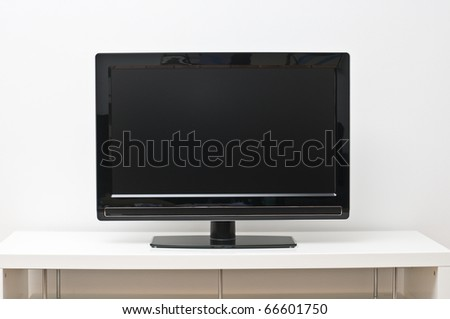 Black flat screen tv set on white table and wall