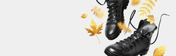 Black flying leather men's or women's boots, autumn golden leaves on light background. Creative concept of autumn shoes. Fashionable stylish hiker boots. Minimalistic footwear Mock up. Unisex boots