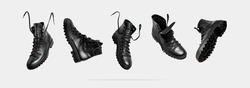 Black flying leather men's or women's boots isolated on light gray background. Fashionable stylish hiker boots. Creative minimalistic shoes background. Rough unisex boots. Layout with footwear Mock up