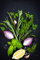 Black food background with fresh aromatic herbs. red onion and lemon, top view