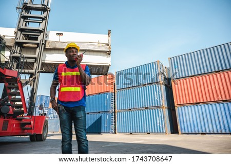 Black foreman worker working control the crane and forklift at Container cargo harbor to loading containers. African dock male staff with radio for Logistics import export shipping concept. Zdjęcia stock ©