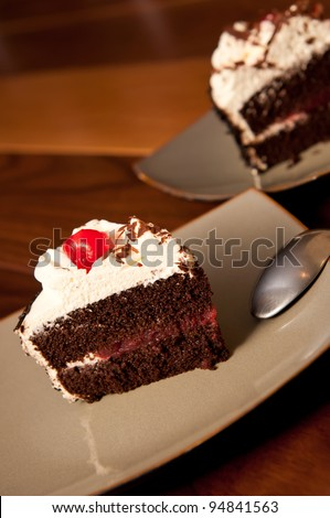 Black forest cake on a dark plate with a maraschino cherry and spoonBlack Forest Cake with maraschino cherry