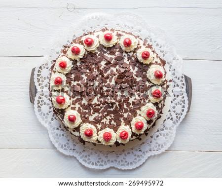 Black Forest cake on white wooden.