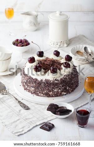 Black forest cake, Schwarzwald pie, dark chocolate and cherry dessert on a white wooden cutting board.