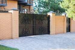 Black forged automatic gates in the cottage